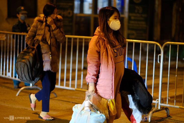 Một số người mang đồ đạc đi ra khỏi khu vực bị chốt chặn ở phố Trúc Bạch. (Nguồn: EVN).