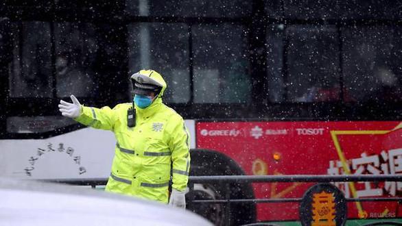 Cảnh sát điều khiển giao thông giữa trời tuyết rơi ở Vũ Hán, thành phố tâm dịch thuộc tỉnh Hồ Bắc, Trung Quốc ngày 15-2 – Ảnh: REUTERS